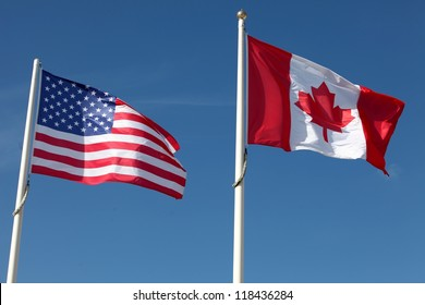 American and Canadian flags waving against a blue sky