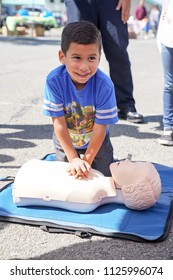 American Canyon, CA/USA- 03/25/2017: Child practices hands only CPR at Fire & Rescue CPR training booth at community event.