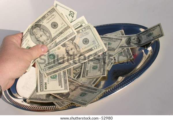 american cash on a silver platter, piled high with a human hand holding some of it above the tray with a white background