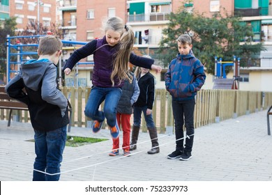 american children playing rubber band jumping game and laughing outdoors