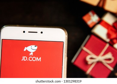 American Chinese e-commerce company JD.com logo is seen on an Android mobile device with a Christmas wrapped gifts in the background.