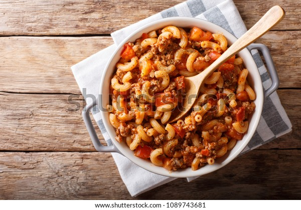 american chop suey, american goulash, with elbow pasta, beef and tomatoes close-up in a saucepan. horizontal top view from above