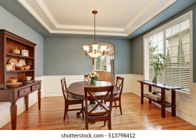 American classic dining room interior with green walls, vintage wooden cupboard, hardwood floor. Decorated with fresh roses in a vase. Northwest, USA