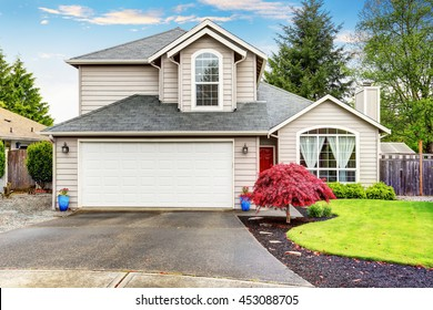 American classic home with beige exterior paint. Beautiful curb appeal.