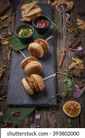 American Classic Mini Cheese Burgers in Sticks served with duo dips on hot stone, wooden background