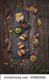 American Classic Mini Cheese Burgers in Sticks served with Duo Dipping Sauces and Potato Fries on Hot Stone, on Wooden Background