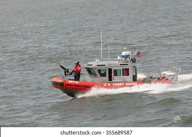 AMERICAN COAST GUARD VESSEL UNDERWAY NEW YORK - CIRCA  2013 - US Coast Guard patrol boat with officer manning gun on the bow patrolling on New York Harbor NY USA