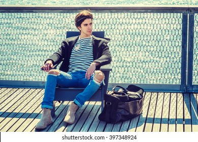 American college student traveling in New York, wearing fashionable coat, striped undershirt, jeans, boots, carrying duffel leather bag, sitting on dock by river, relaxing. Instagram filtered effect.