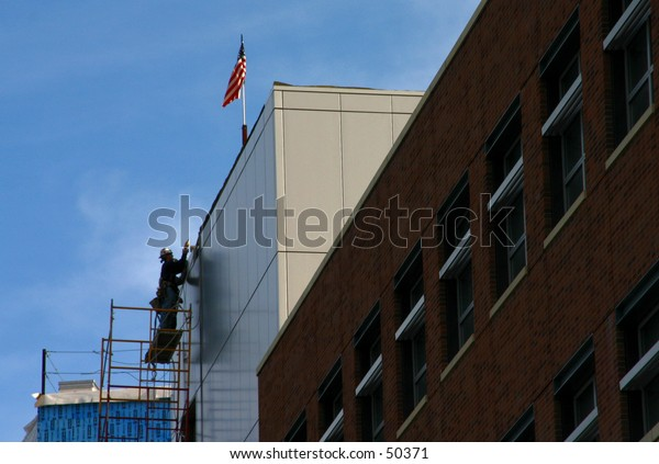 American construction working on building with flag visible