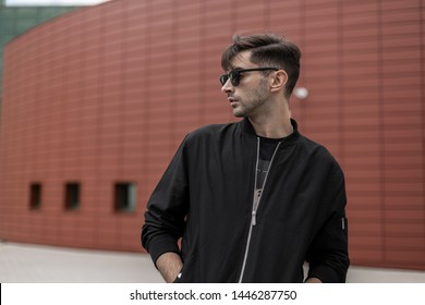 American cool young hipster man in a fashionable jacket in stylish sunglasses with trendy hairstyle walks in the city on a summer day. Handsome guy model near the red building outdoors. Street style.