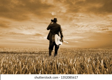 the american cowboy with his classic guitar at the countryside of texas on a sunset evening