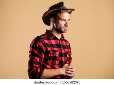 American cowboy. Western life. Man unshaven cowboy beige background. Unshaven guy in cowboy hat. Handsome bearded macho. Beauty standard. Example of true masculinity. Cowboy wearing hat.