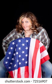 An American Cowgirl sitting on a chair with a flag on it.