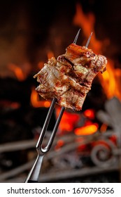 American cuisine. Fried pork ribs with honesty, chopped on a fork against a fire. The cook holds a fork in his hand. background image, copy space text