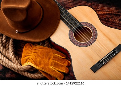 American culture, living on a ranch and country muisc concept theme with a cowboy hat, acoustic guitar, farm gloves and a rope lasso on a wooden background in a old saloon