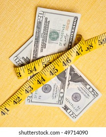 American currency is squeezed by a yellow measuring tape on a measuring background to demonstrate that money is tight.