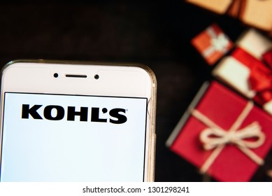 American department store retailing chain company Kohl's logo is seen on an Android mobile device with a Christmas wrapped gifts in the background.