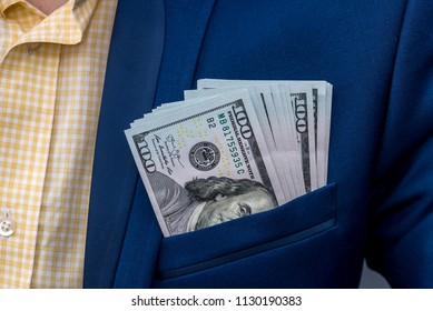 American dollar banknotes in businessman jacket's pocket