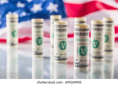 American dollar banknotes rolled in different positions and USA flag in the background.