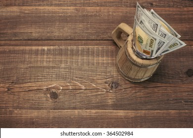 American Dollar Bills In The Wood Bear Mug Top View On The Rough Wooden Table Background With Copy Space