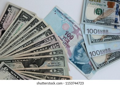 American Dollar,Euro and Turkish Lira banknotes on the white surface.Exchange rate between of them.Turkish hundred banknote between dollar and euro banknotes.Close up taken,top view.