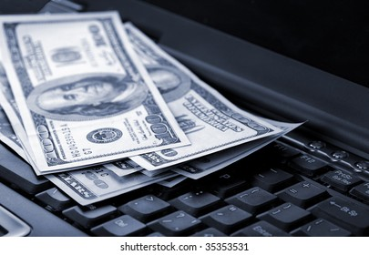 American dollars laying on laptop toned blue