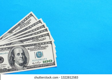 American dollars. A stack of hundred dollar bills on a blue background. Flat lay, top view, copy space