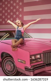 American dream girl in pink and jeans at pink cadillac stars and stripes