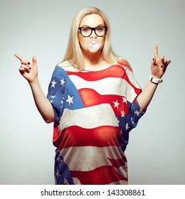 American Dream (Lifestyle) Concept: Young pregnant woman in american flag like dress and trendy glasses chewing bubble gum and dancing over gray background. Hipster style. Studio shot