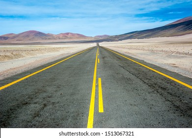 American empty desert asphalt road from low angle with mountains and clouds on background. South american highway in Atacama desert, Chile. Yellow striped road.