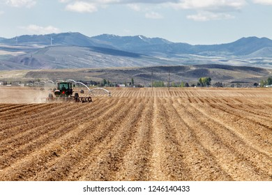 American Falls, Idaho, USA May 2, 2012 A tractor in a farm field  plowing the soil in preparation for spring planting.