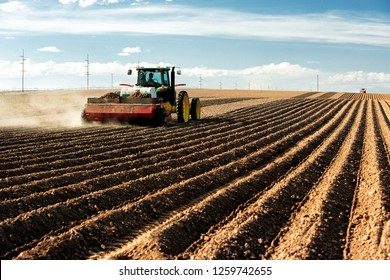 American Falls, Idaho, USA May 10, 2017 A farmer using a tractor and planting implement, plants potatoes in the fertile farm fields of Idaho.