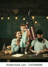 American family at desk with son making paper planes. Parents teaching son american traditions playing. Kid with parents in classroom with usa flag, chalkboard on background. Homeschooling concept