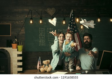 American family at desk with son play with paper planes. Homeschooling concept. Kid with parents in classroom with usa flag, chalkboard on background. Parents teaching son american traditions playing