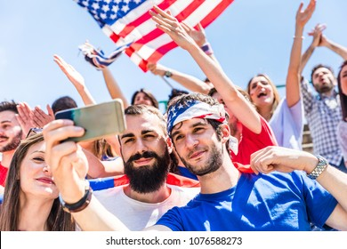 American fans taking a selfie at stadium during a match with fellow supporters and USA flags on background. Group of supporters watching a match and cheering team USA. Sport and lifestyle concepts.