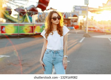 American fashionable redhead young hipster woman in vintage blue jeans in a stylish t-shirt in trendy sunglasses walk in an amusement park at sunset. Cute girl model enjoys the weekend.