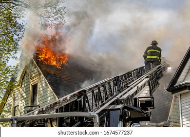 American firefighter on fire truck ladder as flames vent through the roof at the scene of a house fire