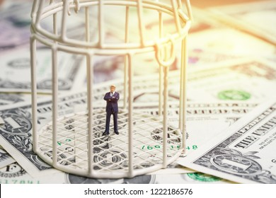 American first, financial war under protection, miniature businessman president inside birdcage on pile of US dollar banknotes, metaphor of limited thinking, money trap or anti globalization.
