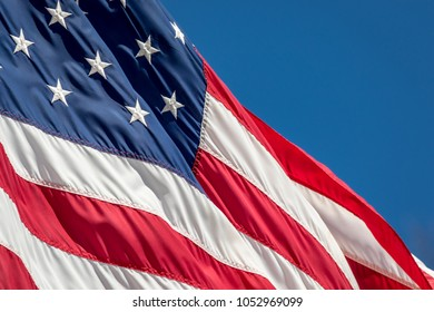 American Flag adorned with stars and stripes waves in the wind against a blue sky