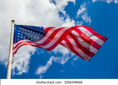 American flag against a blue sky with clouds