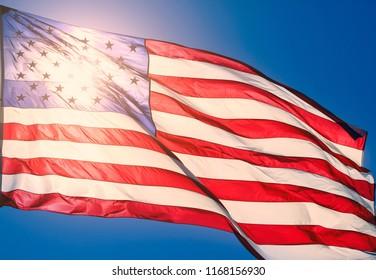 American flag against the sun