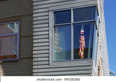 American flag in an apartment behind a corner window of a modern building