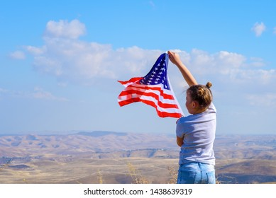 American flag. Back view little patriotic happy girl holding USA flag waving on blue sky background. . National 4 july. Memorial day.