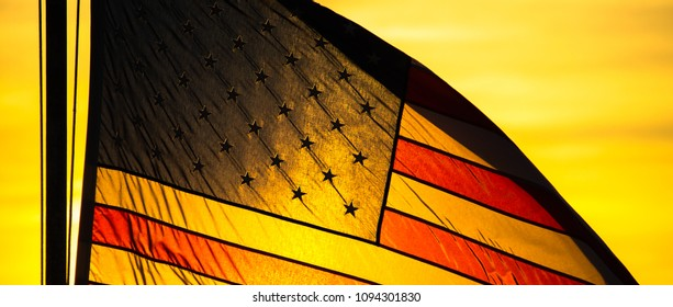 An American flag backlit with golden sunlight at sunset.