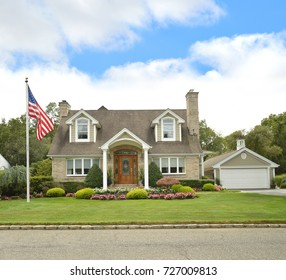 American Flag Beautiful Suburban Brick Cape Cod style home blue sky clouds USA
