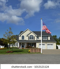 American flag Beautiful Suburban Yellow McMansion Home blue sky clouds USA
