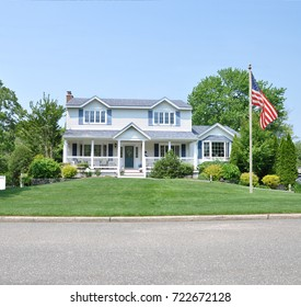 American Flag Beautiful Two Story White Suburban Home with Blue Shutters Blue Sky USA