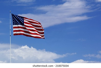 American Flag blowing in the breeze against clear blue sky and white puffy clouds in america