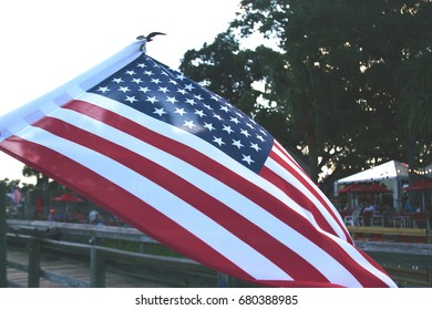 American flag blowing in the breeze, on the boardwalk along the saltmarsh, selective focus