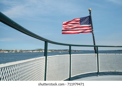 American flag blowing in breeze at stern of passenger ferry crossing Sinclair Inlet from Bremerton, Washington to Port Orchard, Washington with Puget Sound Naval Shipyard in background